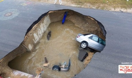 Massive sinkhole swallows two cars, leaving one dead